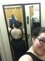 Selfie taken in a mirror to show the back of a black dress that is essentially backless.