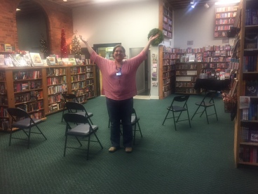 Picture of a bookstore a white woman with short brunette hair in a red shirt and jeans stand in the middle of a room with green carpet with her arms up and out. There are chairs behind her, and bookcases surround the outside of the room.