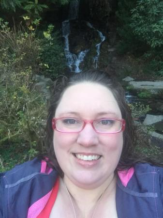 Selfie of a white fat woman with long brunette hair, pink glasses, and a grey and pink jacket in the foreground with a waterfall, rocks, and bushes in the background.