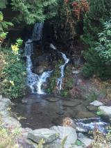 Picture of a pool of water surrounded by rocks and greenery in the foreground with a double waterfall in the background