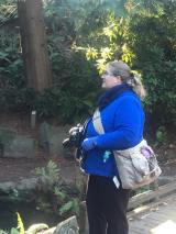 Picture with woods, rocks and greenery on the left and a fat blond woman in a blue sweater, gloves, and scarf and black pants holding a camera with a camera bag across her body.